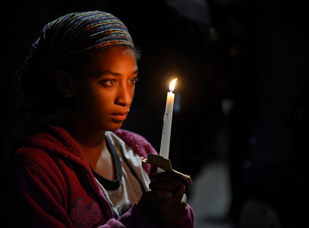 . A woman holds a candle during a vigil at the Fruitvale BART station in Oakland, Calif., on Friday, July 19, 2013. People gathered to demonstrate in the week following the acquittal of George Zimmerman in the shooting death of Trayvon Martin. (AP Photo/Bay Area News Group, Jose Carlos Fajardo)