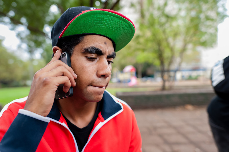 Young Aboriginal Man listening pensively on mobile phone