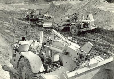 Três, MOTOR SCRAPERS, auxiliadas por um potente BULLDOZER maquinas de grande rendimento trabalham na remoção de terras.