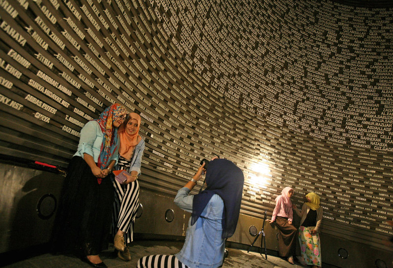. Acehnese women have their photo taken near the wall displaying the names of the victims of 2004 Indian Ocean tsunami, at the Tsunami Museum in Banda Aceh, Aceh province, Indonesia, Wednesday, Dec. 24, 2014. Aceh, the worst-hit region by Indian Ocean tsunami, is preparing to commemorate the 10th anniversary of the Boxing Day tsunami that killed more than 100,000 people in the province. (AP Photo/Binsar Bakkara)