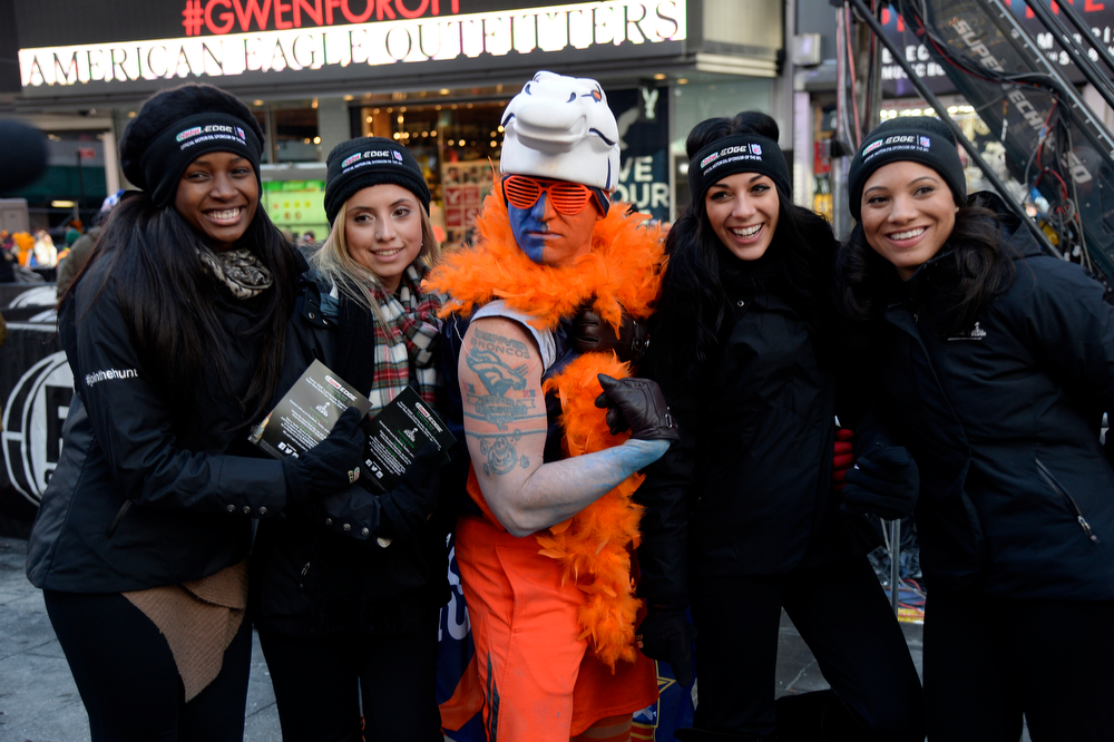 Description of . Denver Broncos fan Lonnie Mareno poses with the Castrol Edge girls as Super Bowl XLVlll fans hit Times Square to enjoy the Super Bowl Boulevard. The NFL transformed a portion of Broadway into the sports and entertainment hub of Super Bowl Week, January 29, 2014. (Photo by John Leyba/The Denver Post)