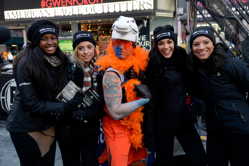 . Denver Broncos fan Lonnie Mareno poses with the Castrol Edge girls as Super Bowl XLVlll fans hit Times Square to enjoy the Super Bowl Boulevard. The NFL transformed a portion of Broadway into the sports and entertainment hub of Super Bowl Week, January 29, 2014. (Photo by John Leyba/The Denver Post)
