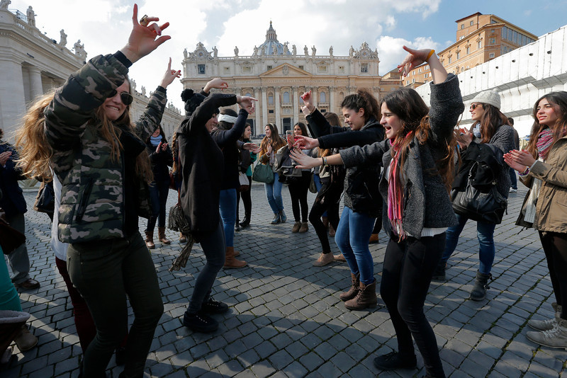 . Young women from Spain dance in St. Peter\'s Square, at the Vatican, Thursday, Feb. 28, 2013. Shortly before 5 p.m. on Thursday, Pope Benedict XVI will leave the Apostolic palace inside the Vatican for the last time as pontiff, head to the helipad at the top of the hill in the Vatican gardens and fly to the papal retreat at Castel Gandolfo south of Rome. There, at 8 p.m. sharp, Benedict will become the first pontiff in 600 years to resign. (AP Photo/Dmitry Lovetsky)