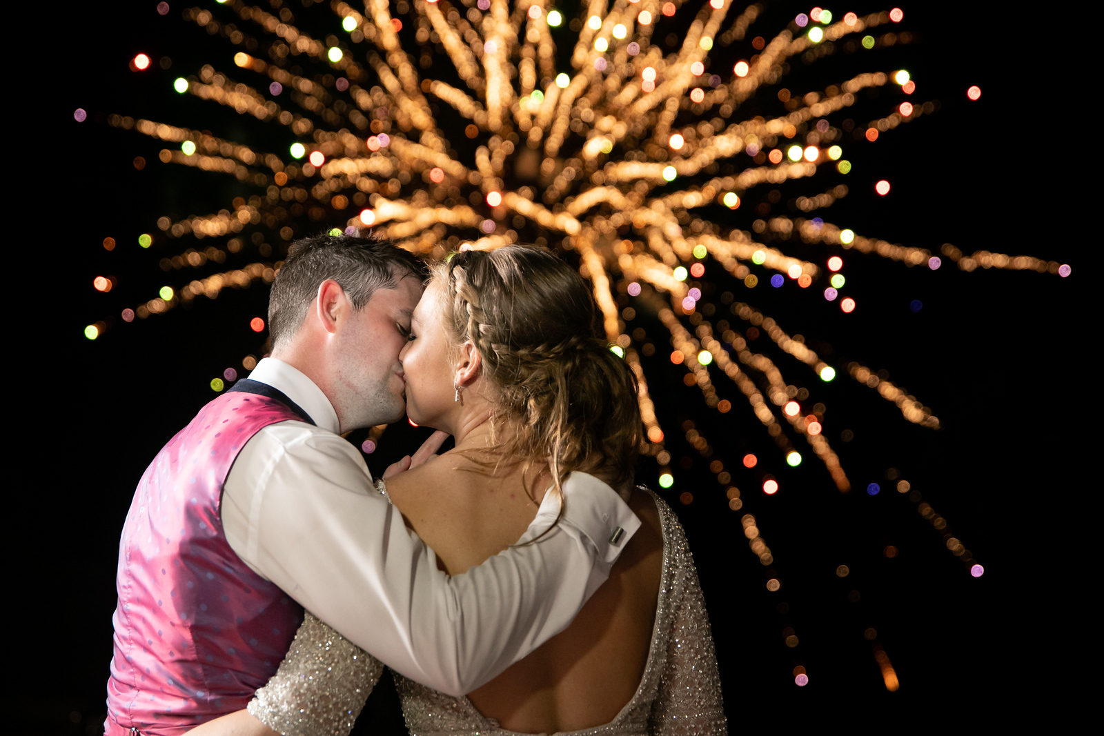 newlywed couple kissing with fireworks going off behind them on their wedding night