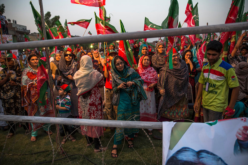 . Supporters wave flags and cheer as they watch Imran Khan, chairman of the Pakistan Tehrik e Insaf (PTI) party, arrive during an election campaign rally on May 05, 2013 in Faisalabad, Pakistan. Pakistan\'s parliamentary elections are due to be held on May 11. (Photo by Daniel Berehulak/Getty Images)