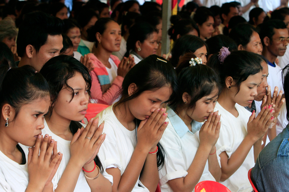 Description of . Cambodian garment workers offer prayers during a rally celebrating the International Human Rights Day in Phnom Penh, Cambodia, Monday, Dec. 10, 2012. About one thousand participants consist of non-governmental organization activists, garment workers, and international diplomats on Monday marched on the street in Phnom Penh, calling for the protection of human rights. (AP Photo/Heng Sinith)