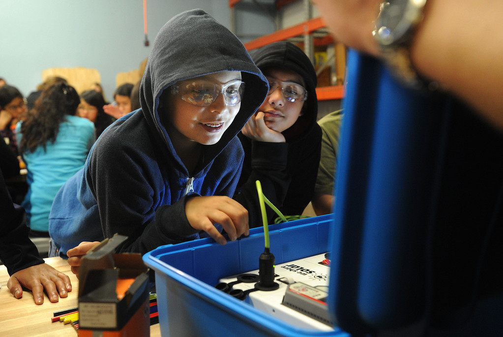 . Andres Leal, left, and Luis Merino, both 11 and of San Jose, smile as they plug in a light to test a solar suitcase at the Tech Museum in San Jose, Calif., on Monday, Jan. 21, 2013. As part of Dr. Martin Luther King Jr.\'s legacy of service, young students from around the Bay Area took part in the assembling of WE CARE (Women\'s Emergency Communication and Reliable Electricity) solar suitcases. These suitcases contain a complete solar electric system that will be sent to Sierra Leone, where such kits can be life-changing, bringing light to desperately poor West African schools. The Tech Museum of Innovation is a partner in this program with WE CARE. (Dan Honda/Staff)