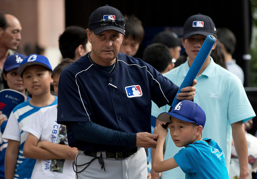 . Rick Dell, director of Baseball Development in Asia for Major League Baseball (MLB), center, teaches a Chinese boy how to bat during an event held at a shopping mall, on  International Children\'s Day in Beijing Saturday, June 1, 2013. (AP Photo/Andy Wong)