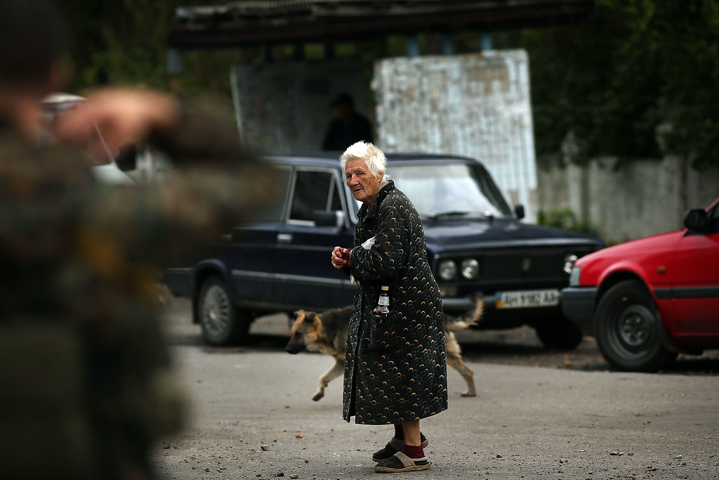 . ALOVAISK, UKRAINE - SEPTEMBER 10:  An elderly woman walks through the streets of a town which was damaged during heavy fighting in August on September 10, 2014 in Alovaisk, Ukraine. Alovaisk, which is about an hour outside of the separatist held city of Donetsk, saw sustained shelling in August and is still the site of fighting between Ukrainian troops and the Russian backed separatists. Sporadic shelling is heard in Donetsk daily and gunfire in the port city of Mariupol. The city of Donetsk has only around 300,000 people remaining out of a population of 900,000 due to the fighting.  (Photo by Spencer Platt/Getty Images)