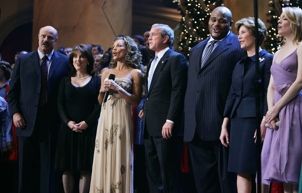 . President and first lady Laura Bush join host Dr. Phil, left, and Robin McGraw, second left, and performers Vanessa Williams, third left, Ruben Studdard, third right, and LeAnn Rimes, right, during taping of the annual Christmas in Washington concert, at the National Building Museum, Sunday, Dec. 12, 2004, in Washington.   (AP Photo/Manuel Balce Ceneta)
