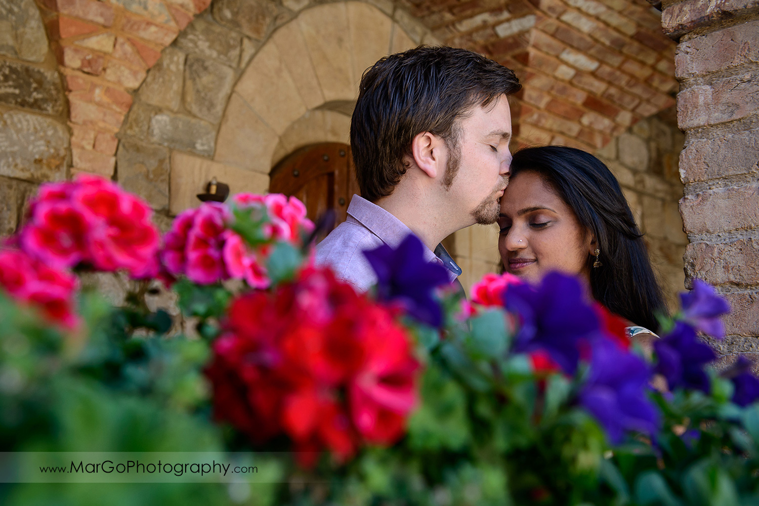 portrait of man in pink shirt kissing Indian woman in flower dress during engagement session at Castello di Amorosa in Calistoga