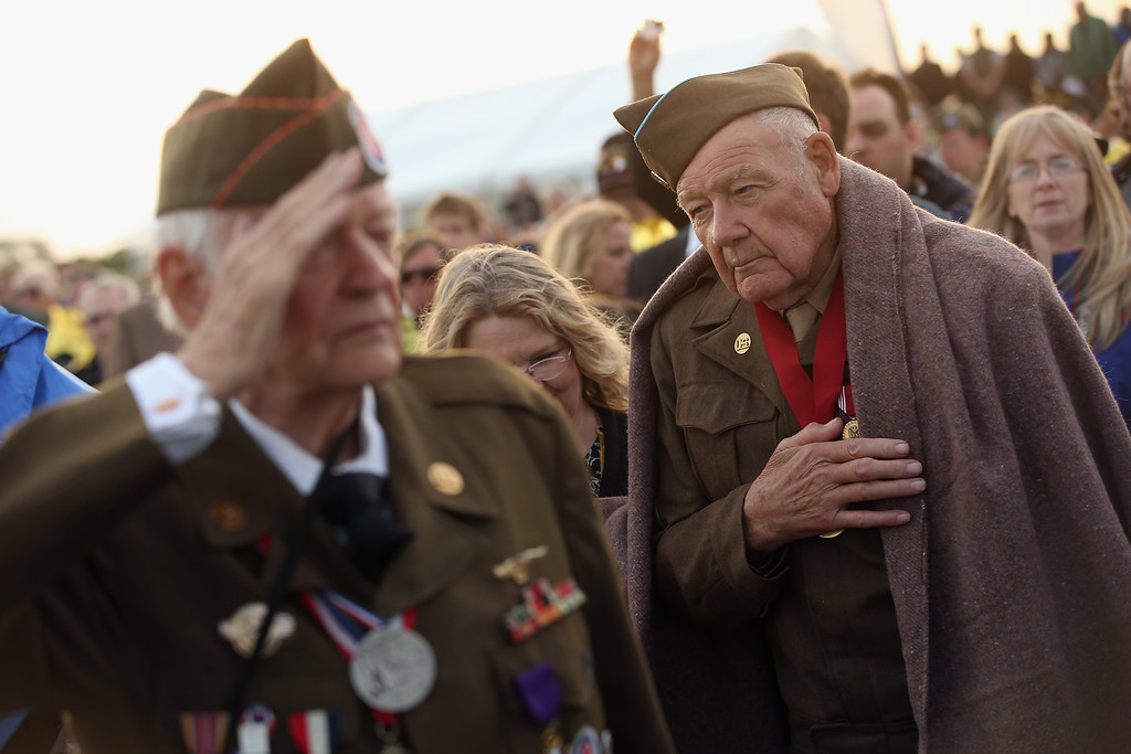 . D-day veterans Frederick Carrier (L), 89, and James McDonald Hamby, 90 of Lenoir, North Carolina, listen to the playing of the U.S. national anthem at the U.S. Ceremony on June 5, 2014 at Utah Beach, France.   (Photo by Sean Gallup/Getty Images)