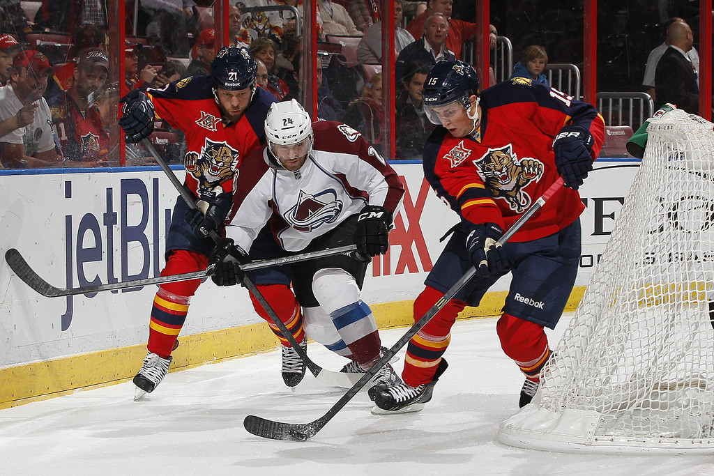 . SUNRISE, FL - JANUARY 24: Drew Shore #15 of the Florida Panthers and Marc-Andre Cliche #24 of the Colorado Avalanche battle for control of a loose puck behind the net at the BB&T Center on January 24, 2014 in Sunrise, Florida. (Photo by Joel Auerbach/Getty Images)