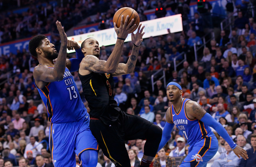 . Cleveland Cavaliers guard George Hill (3) shoots between Oklahoma City Thunder forward Paul George (13) and forward Carmelo Anthony (7) during the first half of an NBA basketball game in Oklahoma City, Tuesday, Feb. 13, 2018. (AP Photo/Sue Ogrocki)