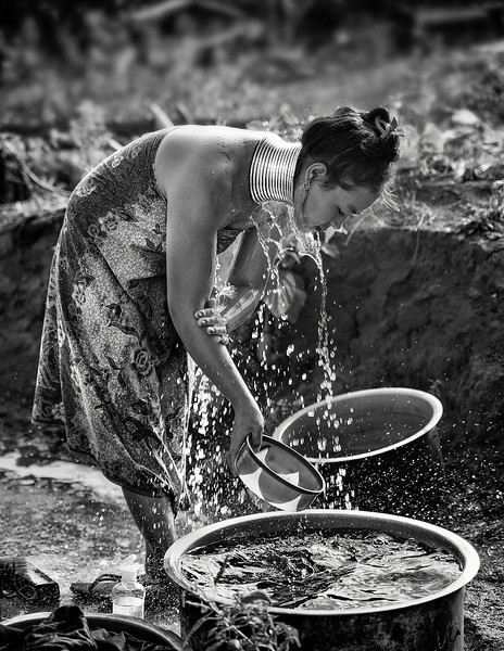 A young woman from the Kaya tribe washing herself in her back yard.   Kayan State, Myanmar, 2017.