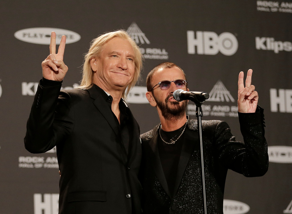 . Joe Walsh and Ringo Star hold up peace signs at the Rock and Roll Hall of Fame Induction Ceremony Saturday, April 18, 2015, in Cleveland. (AP Photo/Tony Dejak)