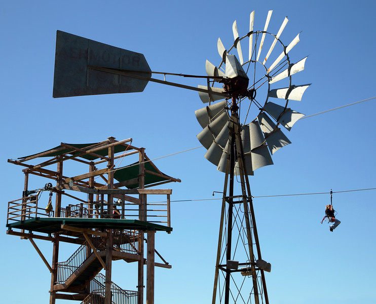 Climbers can zip-line to another part of the Canopy Challenge.  Windmill in foreground.