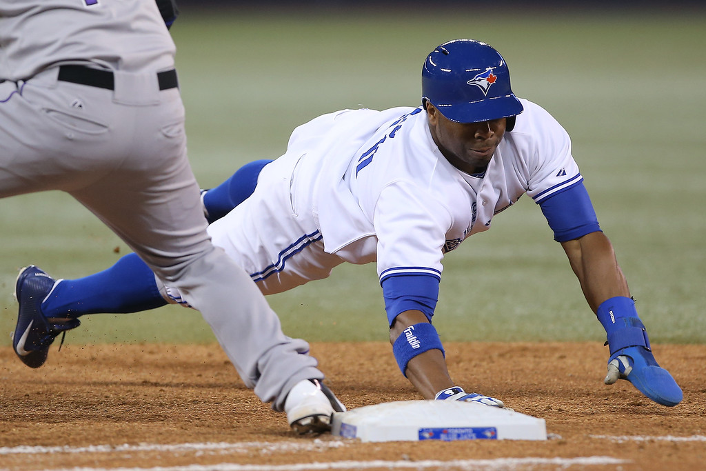 . Rajai Davis #11 of the Toronto Blue Jays dives back to first base on a pick-off attempt during MLB game action against the Colorado Rockies on June 19, 2013 at Rogers Centre in Toronto, Ontario, Canada. (Photo by Tom Szczerbowski/Getty Images)