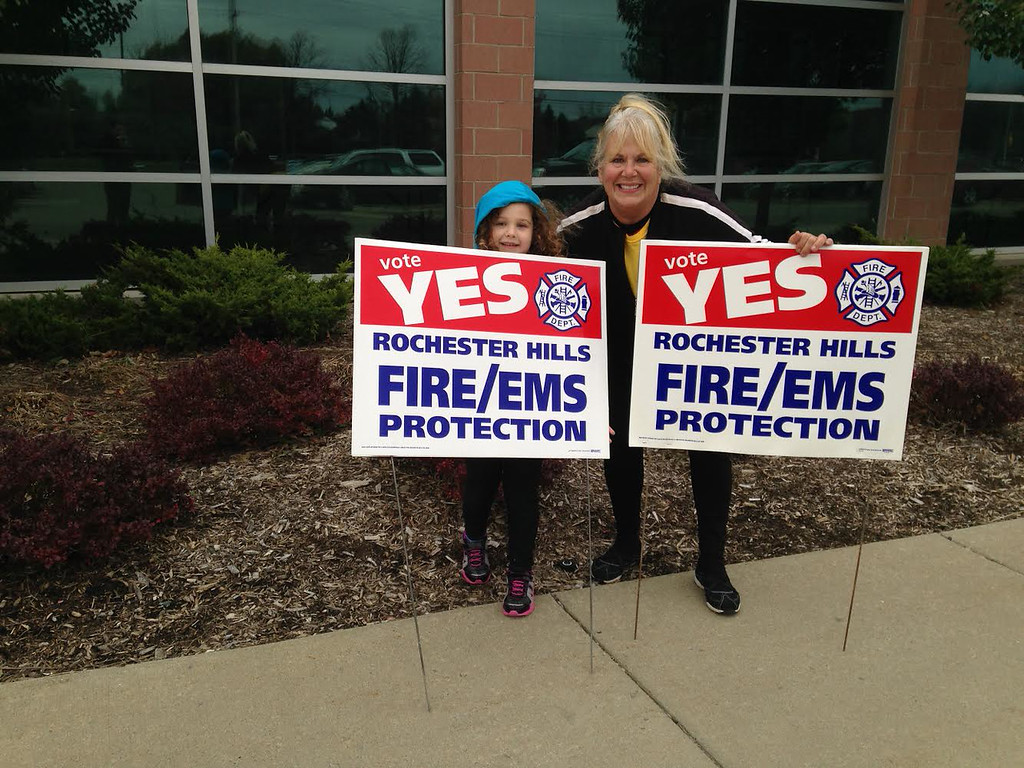 . Rochester Hills resident and former firefighter Linda Raschke and granddaughter Makayla Raschke support a ballot proposal outside a polling location at Rochester Adams High School Tuesday, Nov. 4. The city asked voters to approve a charter amendment which would allow the city to increase the amount of funding dedicated to fire and emergency services. Photo by Paul Kampe/Of The Oakland Press