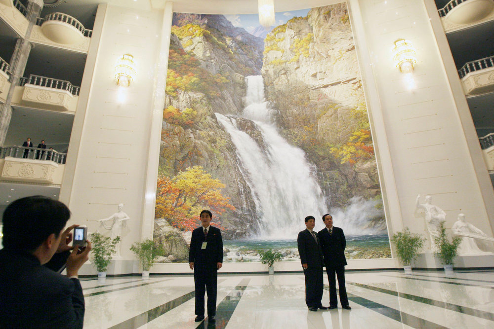 . North Korean men take photos of one another inside the main atrium of the East Pyongyang Grand Theater at the end of a concert by the New York Philharmonic in Pyongyang, North Korea on Tuesday, Feb. 26, 2008.  (AP Photo/David Guttenfelder)