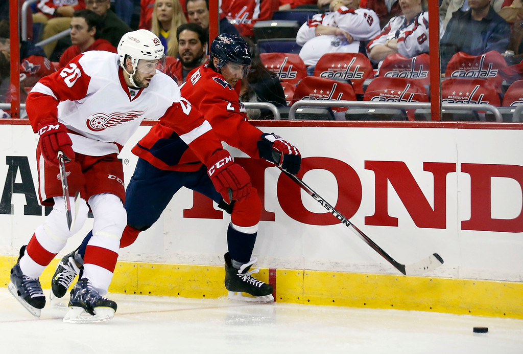 . Detroit Red Wings left wing Drew Miller (20) and Washington Capitals defenseman Matt Niskanen (2) go for the puck in the second period of an NHL hockey game, Wednesday, Oct. 29, 2014, in Washington. (AP Photo/Alex Brandon)