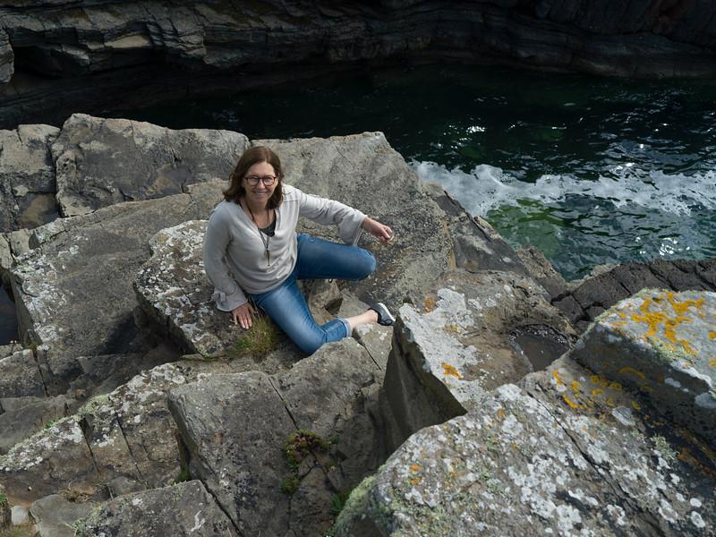 Woman sitting on rocky coastline, Mullaghmore Peninsula, County Sligo, Ireland