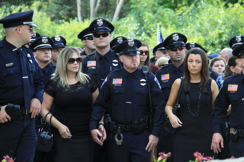 . Police officers from Mendota Heights and West St. Paul arrive at St. Stephen\'s Lutheran Church in West St. Paul for the funeral of Mendota Heights police officer Scott Patrick on Wednesday.  (Minnesota Department of Public Safety Pool Photo: Jen Longaecker)