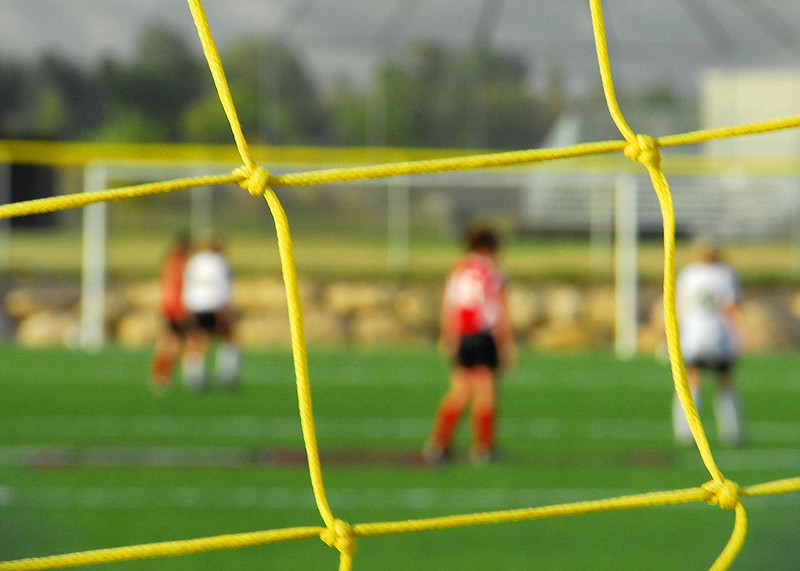 10/2/07 – I was walking past this girl's soccer game. I had no idea who was playing but thought I might be able to create an interesting shot. Since I didn't know anyone, I focused on the goalie's net to frame an out- of-focus player in the distance. It worked for me.
