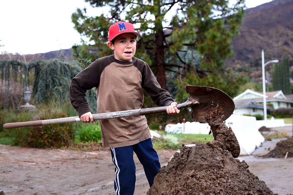 . Max Loera, 9, helps clean up mud at Trish Emery\'s home on Rainbow Drive in Glendora Saturday, March 1, 2014. The neighborhood sits below the Colby Fire burn area. (Photo by Sarah Reingewirtz/Pasadena Star-News)