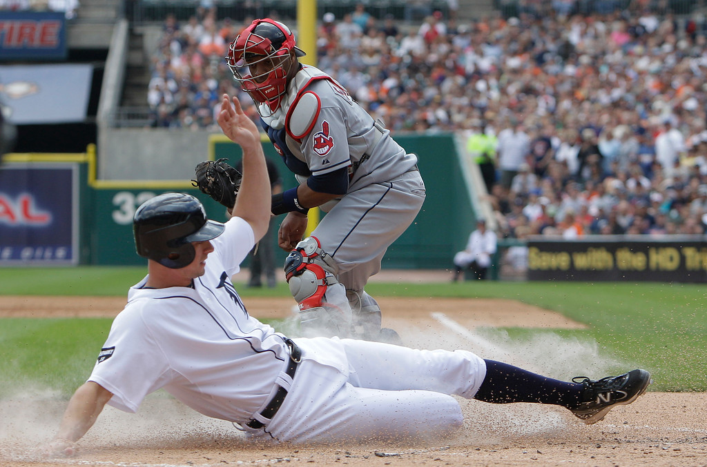. Detroit Tigers\' Don Kelly safely beats the tag of Cleveland Indians catcher Carlos Santana to score during the first inning of a baseball game in Detroit, Thursday, June 16, 2011. Kelly scored from third on a sacrifice fly by Victor Martinez. (AP Photo/Carlos Osorio)