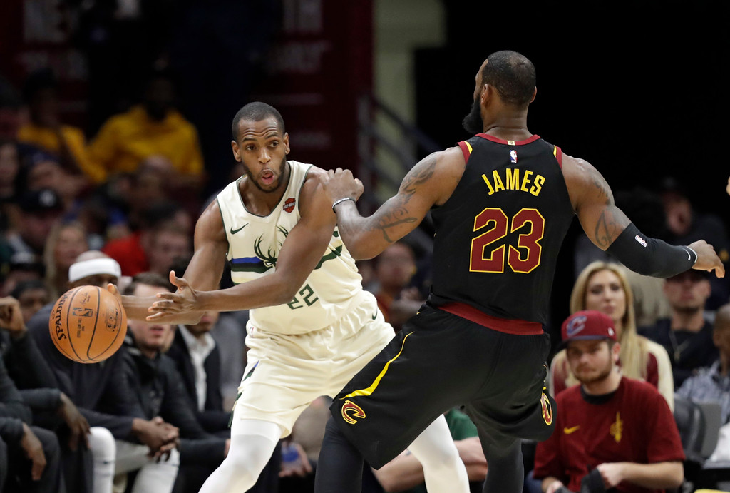 . Milwaukee Bucks\' Khris Middleton (22) passes against Cleveland Cavaliers\' LeBron James (23) in the first half of an NBA basketball game, Monday, March 19, 2018, in Cleveland. (AP Photo/Tony Dejak)