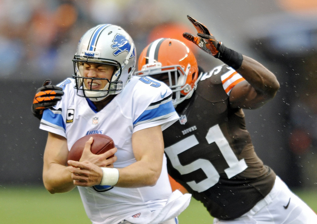 . Detroit Lions quarterback Matthew Stafford is chased by Cleveland Browns linebacker Barkevious Mingo in the second quarter of an NFL football game Sunday, Oct. 13, 2013 in Cleveland. (AP Photo/David Richard)
