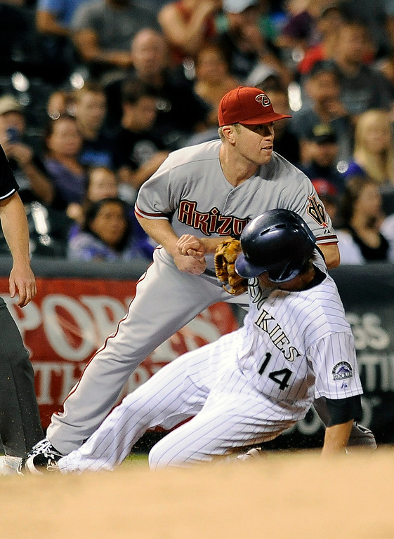 . Colorado Rockies\' Josh Rutledge, bottom, slides safely past Arizona Diamondbacks second baseman Aaron Hill, top, at third base in the third inning of a baseball game Thursday, Sept. 18, 2014, in Denver. (AP Photo/Chris Schneider)