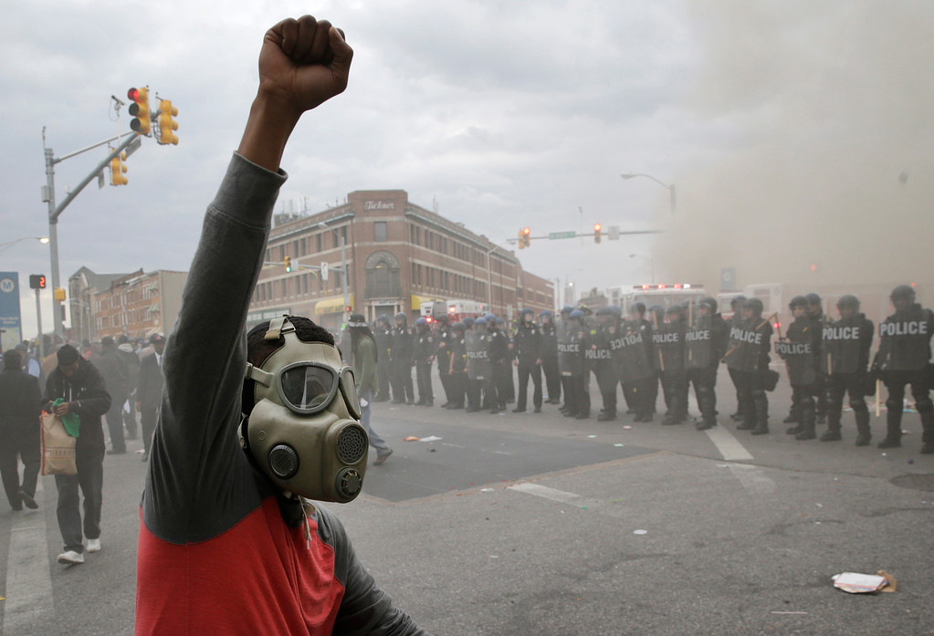. A demonstrator raises his fist as police stand in formation as a store burns, Monday, April 27, 2015, during unrest following the funeral of Freddie Gray in Baltimore. Gray died from spinal injuries about a week after he was arrested and transported in a Baltimore Police Department van. (AP Photo/Patrick Semansky)