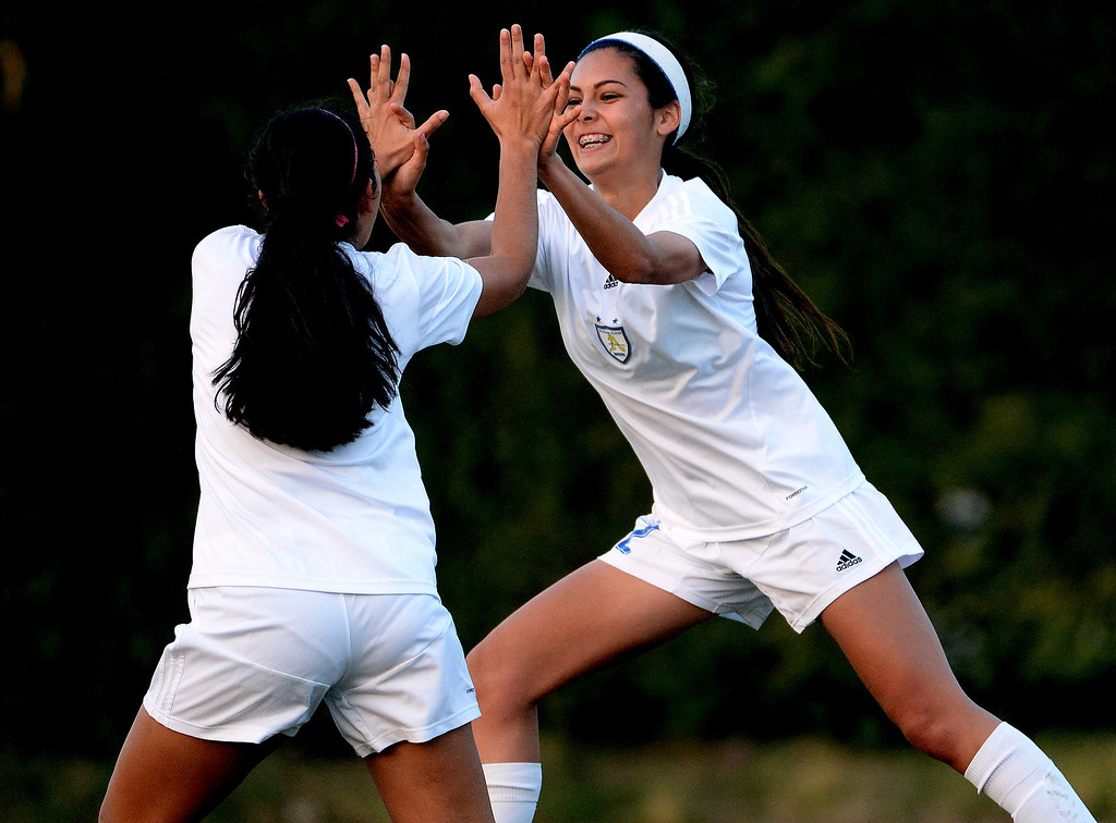 . Bishop Amat\'s Jamie Peters, right, high fives teammate Nicole Diaz after scoring against Marshall in the first half of a prep soccer match at Bishop Amat High School in La Puente, Calif., on Thursday, Jan. 9, 2014.Amat won 3-0. (Keith Birmingham Pasadena Star-News)