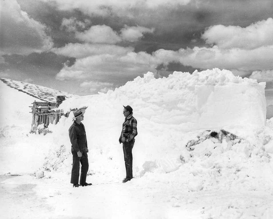 . Ruben Hart and George Swift (right) road foreman in Rocky National Mountain Park, discuss a problem in front of a 12-foot snowdrift north of the Fall River museum in 1955. Swift, who has been in the park since 1926, says there is less snow on the road this year than in any year since it was opened.  (Donald C Cieber/The Denver Post)