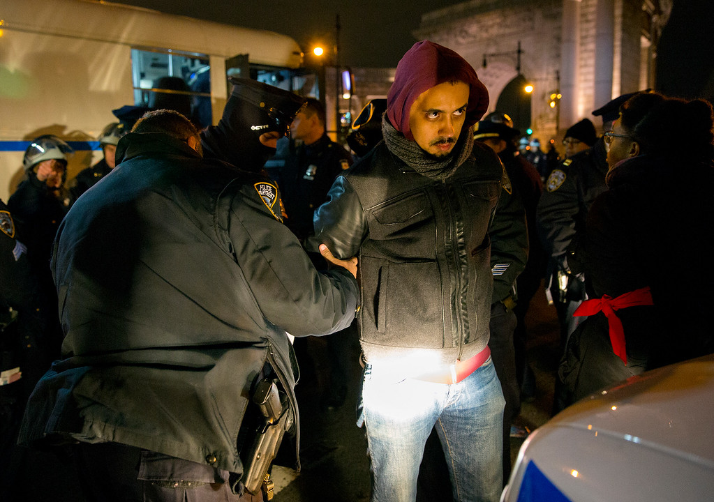 . A person is taken into custody at the Manhattan side of the Manhattan Bridge Thursday, Dec. 4, 2014, in New York, after several protesters were arrested as they tried to block the bridge entrance protesting against a grand jury\'s decision not to indict the police officer involved in the death of Eric Garner. A grand jury cleared a white New York City police officer Wednesday in the videotaped chokehold death of Garner, an unarmed black man, who had been stopped on suspicion of selling loose, untaxed cigarettes, a lawyer for the victim\'s family said. (AP Photo/Craig Ruttle)