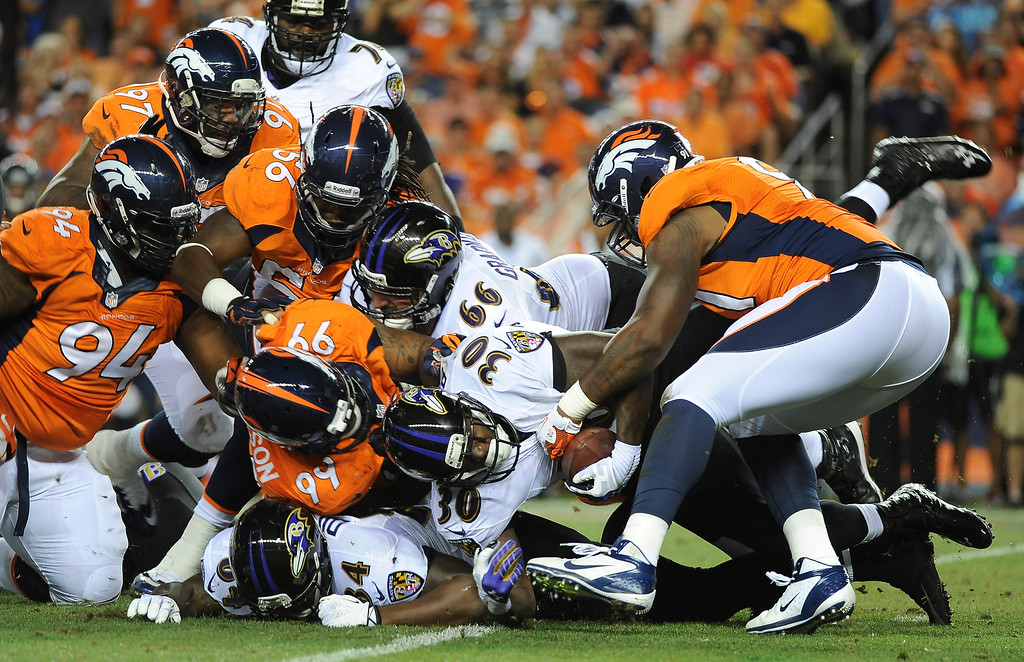 . A host of Denver Broncos defenders bottle up Baltimore Ravens running back Bernard Pierce in the second quarter at Sports Authority Field at Mile High on September 5, 2013. (Photo by Steve Nehf/The Denver Post)