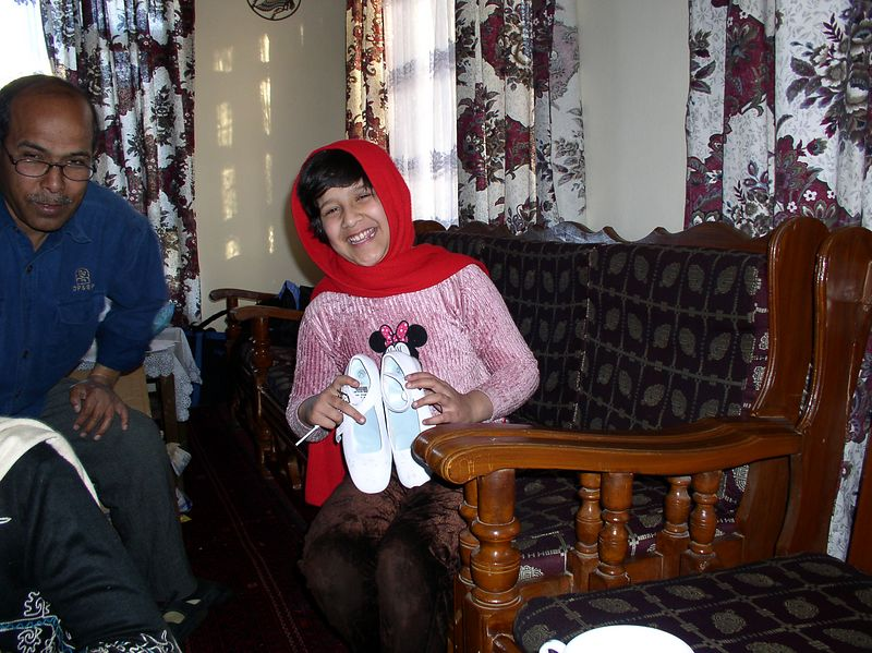 Oh how happy Meetsa was to get these white party shoes. She is Pashtoon's daughter. Her father, Dr. Azfar, is next to her. The family spent the last 10 years (most of Meetsa's l;ife) as refugees in Pakistan. They fled Afghanistan with the clothes on their backs. They returned last summer.