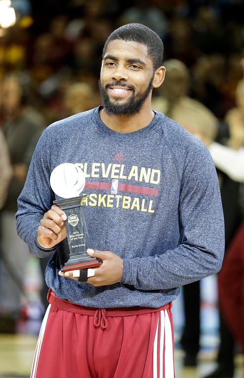 . Cleveland Cavaliers\' Kyrie Irving holds his Male Athlete of the Year award from USA Basketball before an NBA basketball game against the Memphis Grizzlies Sunday, Dec. 21, 2014, in Cleveland. (AP Photo/Mark Duncan)