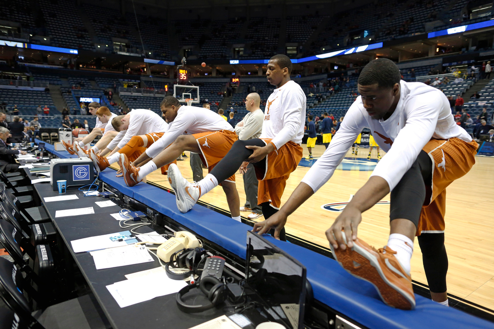 Description of . Texas players stretch before a third-round game against the Michigan of the NCAA college basketball tournament Saturday, March 22, 2014, in Milwaukee. (AP Photo/Jeffrey Phelps)