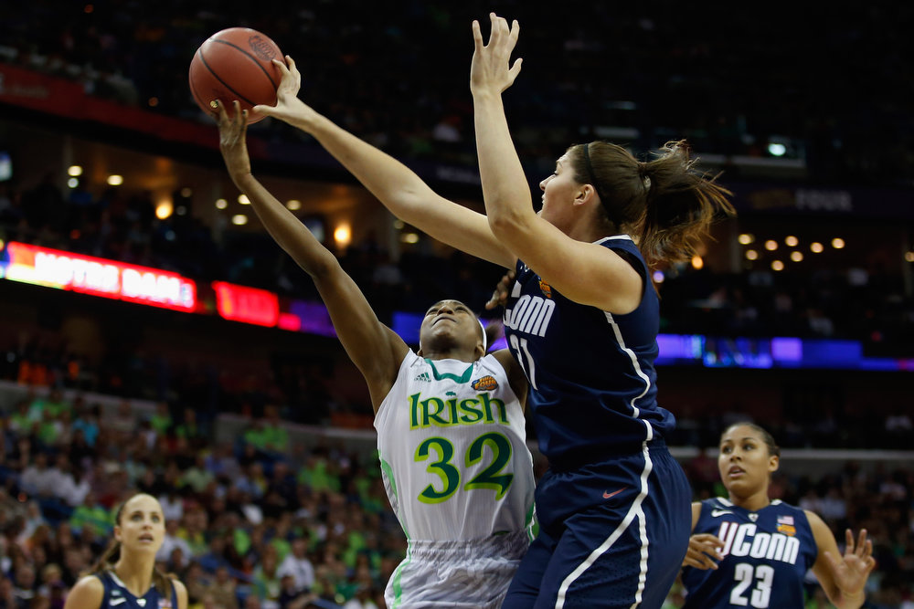 Description of . Stefanie Dolson #31 of the Connecticut Huskies blocks a shot by Jewell Loyd #32 of the Notre Dame Fighting Irish during the National Semifinal game of the 2013 NCAA Division I Women\'s Basketball Championship at the New Orleans Arena on April 7, 2013 in New Orleans, Louisiana.  (Photo by Chris Graythen/Getty Images)