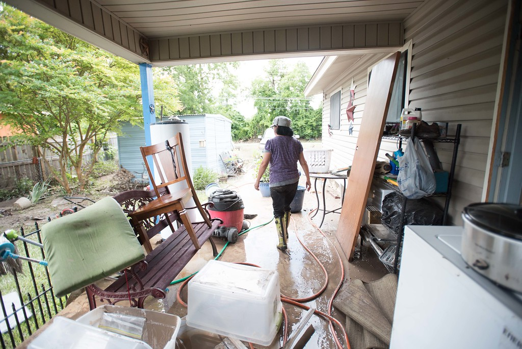 . Amy Schmitt walks through her flood-damaged patio Sunday May 24, 2015, in San Marcos, Texas. Record rainfall was wreaking havoc across a swath of the U.S. Midwest on Sunday, causing flash floods in normally dry riverbeds, spawning tornadoes and forcing at least 2,000 people to flee. (Erika Rich/Austin American-Statesman via AP)  AUSTIN CHRONICLE OUT, COMMUNITY IMPACT OUT, INTERNET AND TV MUST CREDIT PHOTOGRAPHER AND STATESMAN.COM, MAGS OUT