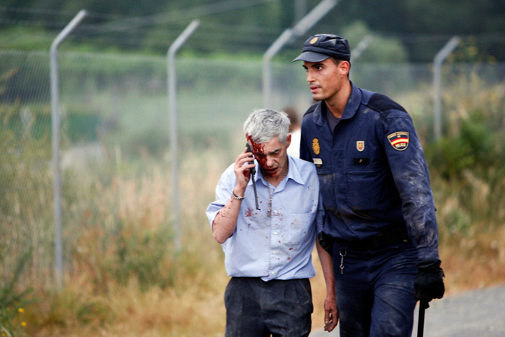 . An injured passenger is helped by a policeman after a train crashed near Santiago de Compostela, northwestern Spain, July 24, 2013.  A woman who was close to the site of the accident told the radio station that she had first heard a loud explosion and then saw the train derailed.    REUTERS/Oscar Corral