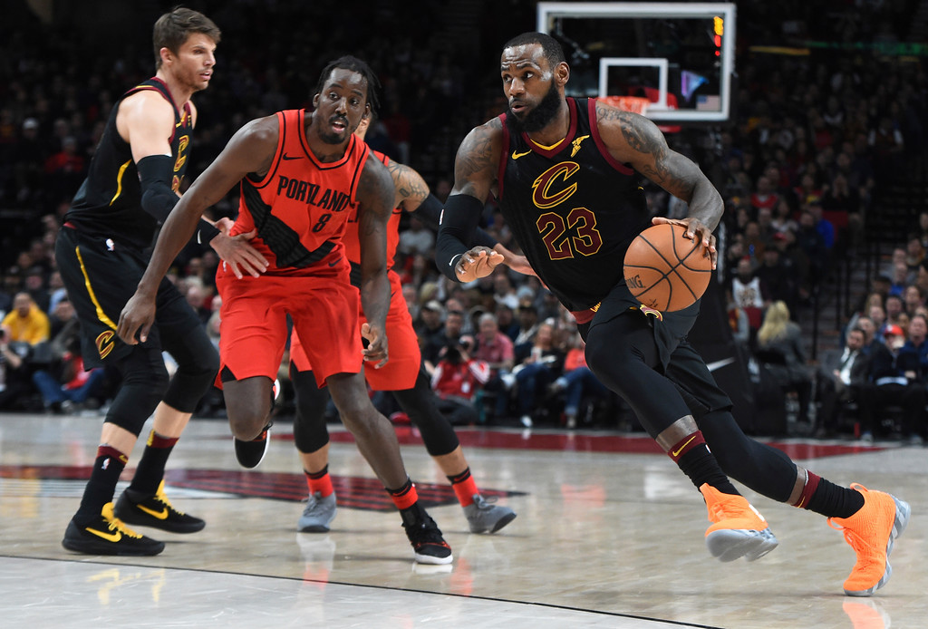 . Cleveland Cavaliers forward LeBron James, right, drives to the basket past Portland Trail Blazers forward Al-Farouq Aminu, center, during the first half of an NBA basketball game in Portland, Ore., Thursday, March 15, 2018. (AP Photo/Steve Dykes)