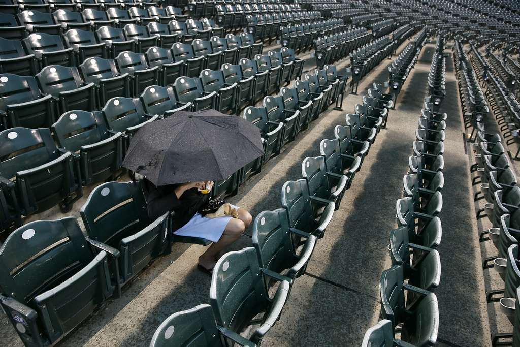. A fan waits out the rain under an umbrella during a rain delay before the start of the game between the Colorado Rockies and the Chicago Cubs at Coors Field on August 7, 2014 in Denver, CO. (Photo by Trevor Brown/Getty Images)