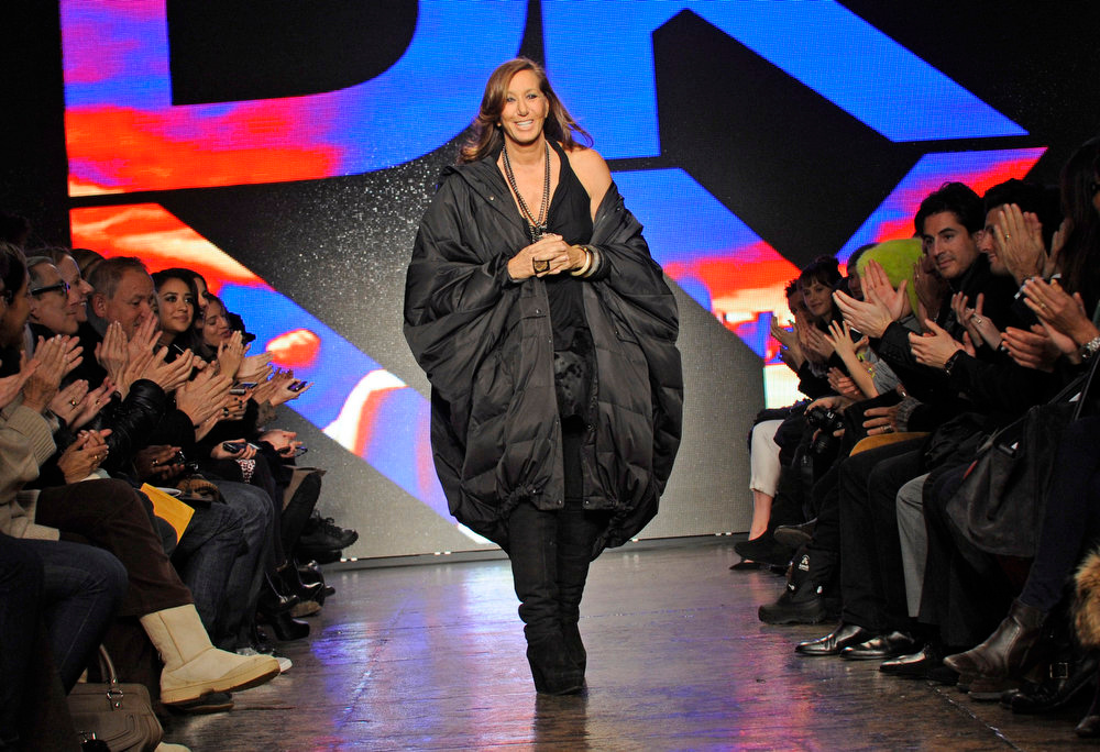 Description of . Donna Karan acknowledges applause after the showing of the DKNY Fall 2013 collection during Fashion Week, Sunday, Feb. 10, 2013, in New York. (AP Photo/Louis Lanzano)
