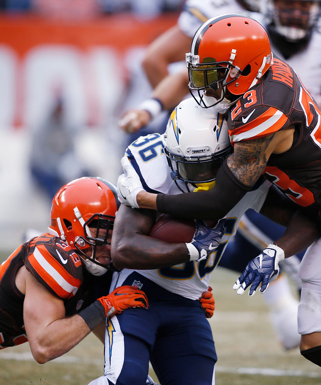 . San Diego Chargers running back Ronnie Hillman (36) is tackled by Cleveland Browns free safety Ed Reynolds (39) and defensive back Joe Haden in the first half of an NFL football game, Saturday, Dec. 24, 2016, in Cleveland. (AP Photo/Ron Schwane)