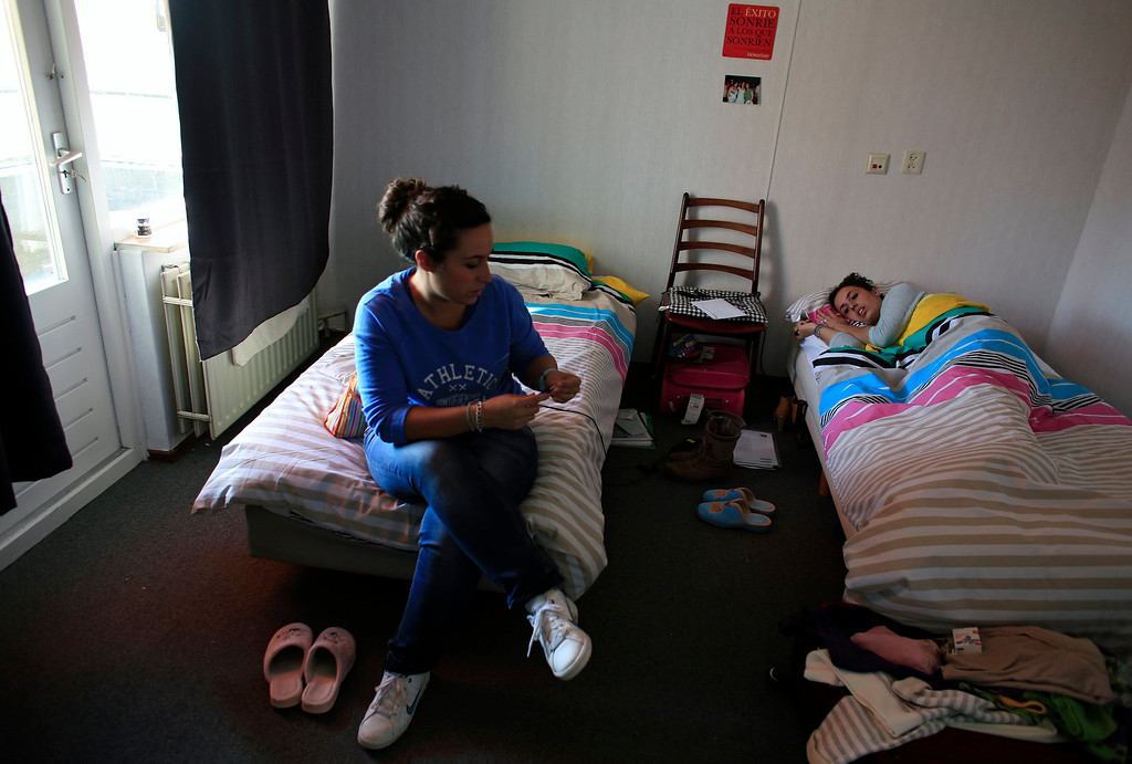 . Spanish nurses Maria Jose Marin (R), 23, and her twin sister Maria Teresa take a rest in their apartment in the Deo Gratias nursing home in The Hague, June 6, 2013. After months of studying Dutch, a group of young Spanish nurses moved to the Netherlands to take up work, fleeing a dismal job market at home. Spain\'s population dropped last year for the first time on record as young professionals and immigrants who moved here during a construction boom head for greener pastures. Spain\'s jobless rate is 27 percent, and more than half of young workers are unemployed. For Spanish nurses, the Netherlands\' nursing deficit is a boon. Picture taken June 6, 2013.  REUTERS/Marcelo del Pozo