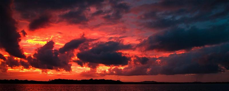 Red colored cumulonimbus cloud, sunset seascape.